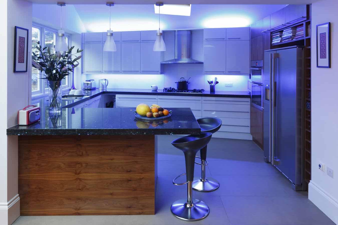 نورپردازی آشپزخانه با منابع نوری مخفی-روشن نمودن میز کار و سطح بالایی کابینت ها. همانطور که می بینید جهت کاهش تاثیر گرمای پخت و پز از رنگ های سرد بهره برده شده است.